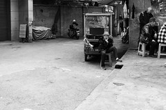 What are you doing here? (Go-tea 郭天) Tags: chongqing républiquepopulairedechine lady woman old men playing sit seated seating guard guardian observation observing observe chair hat kart motorbike motorcycle wait waiting cap clothes hanging hanged wet dry drying laundry street urban city outside outdoor people candid bw bnw black white blackwhite blackandwhite monochrome naturallight natural light asia asian china chinese canon eos 100d 24mm prime portrait