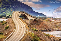 Storseisundet Bridge - Atlantic Ocean Road (Norway) (Andrea Moscato) Tags: light norge europe day view north vivid vista norvegia nynorsk bokmål andreamoscato blue shadow red sky white art history nature yellow clouds artist natura ombre historic cielo luce road street bridge sun mountain architecture fence landscape strada nuvole natural perspective structure ponte montagna naturale green water rock stones tourist attraction