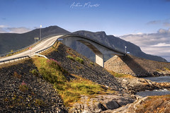 Storseisundet Bridge - Atlantic Ocean Road (Norway) (Andrea Moscato) Tags: andreamoscato norvegia norge bokmål nynorsk north europe view vivid vista day light luce shadow ombre blue white red yellow history historic cielo sky art artist clouds nature natura nuvole natural naturale mountain montagna landscape sun ponte bridge street strada road structure architecture fence perspective water stones rock green tourist attraction sign grass