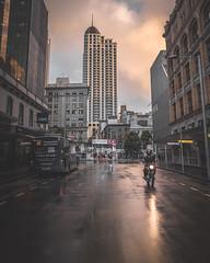 Auckland Metropolis (SnapsByBarrie) Tags: road reflections rain newzealand nz metropolis apartment auckland ricoh gr outside blue sunset street motorbike city clouds winter pink orange bus transport