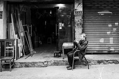 Boring (Go-tea 郭天) Tags: chongqing républiquepopulairedechine boring bored man old alone lonely shop empty desert duty work working wait waiting relax relaxing relaxed seated chair open opned close closed table chairs bricks doors portrait street urban city outside outdoor people candid bw bnw black white blackwhite blackandwhite monochrome naturallight natural light asia asian china chinese canon eos 100d 24mm prime business