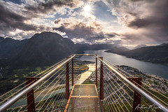 Rampestreken viewpoint - Åndalsnes (Norway) (Andrea Moscato) Tags: andreamoscato norvegia norge bokmål nynorsk north europe view vivid vista day light luce shadow ombre blue white red yellow cielo sky water sea reflection riflesso art artist clouds nature natura nuvole natural naturale fiordo fiord mountain montagna mare landscape deep path trail trekking hiking history historic panorama monument tourist attraction rock stones air overlook fishing village city città cityscape architecture bridge sun sunset dusk tramonto green orange stair brilliant iron perspective