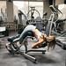 Athlete blonde girl doing leg and body exercise on machine