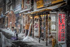 Elderly woman shovels snow (kellypettit) Tags: minakami japan gunma snow shops stores winter cold shop store street streetphotography blizzard shovellingsnow