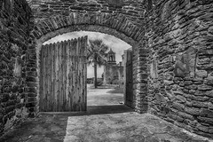 Welcome (writing with light 2422 (Not Pro)) Tags: missionsanjose misiónsanjoséysanmigueldeaguayo sanantonio spanishmission architecture happyfencefriday spanisharchitecture mission texas bw monochrome blackandwhite gate stone arch belltower richborder rich border entrance door entryway