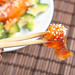 Close-up of a piece of smoked salmon with sesame seeds on chopsticks