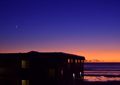 Between day and night (James_D_Images) Tags: sunset dusk crescent moon orange glow horizon pacific ocean shore beach waves silhouette building reflections windows cannonbeach oregon