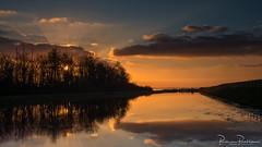 Sun rays and reflections (BraCom (Bram)) Tags: 169 bracom bramvanbroekhoven goereeoverflakkee grevelingen grevelingenmeer herkingen holland nederland netherlands southholland zuidholland avond bomen cloud dijk dike evening fence hek icerink ijsbaan landscape landschap masten masts palen poles reflection sky spiegeling sun sunrays sunset trees water widescreen wolk zon zonnestralen zonsondergang