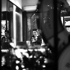 Between the panes (pascalcolin1) Tags: paris femme woman magasin shop vitre panes fenetres windows nuit night reflets reflection glace miroir mirror lumière light photoderue streetview urbanarte noiretblanc blackandwhite photopascalcolin 50mm canon50mm canon
