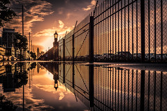 Auckland (SnapsByBarrie) Tags: quaystreet redfence reflections sunset auckland city newzealand nikon nikkor clouds winter rain puddles water ferrybuilding