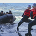 Sailors pull a line affixed to a combat rubber raiding craft with Japan Ground Self-Defense Force.