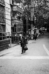 End of the day (Go-tea 郭天) Tags: chongqing républiquepopulairedechine boy young child pupil student shcool backpack schoolbag home walk walking bags carried carry carrying heavy alone lonely end day over road buildings trees back portrait street urban city outside outdoor people candid bw bnw black white blackwhite blackandwhite monochrome naturallight natural light asia asian china chinese canon eos 100d 24mm prime electrtic electricity lines cable