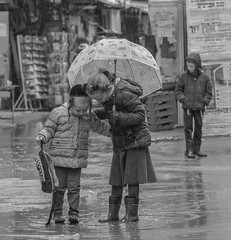 Siblings' Relationships (ybiberman) Tags: israel jerusalem meahshearim children girl boy intimacy portrait candid streetphotography documentary rain umbrella paddle payot kippah boots schoolbox bw blackandwhite