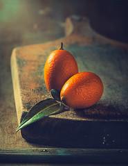 Kumquats (Ro Cafe) Tags: stilllife food fruits citrus orange kumquats cuttingboard wood old darkmood kitchen simple textured naturallight nikkor105mmf28 sonya7iii