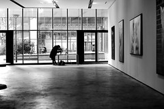 In front of the canvases (pascalcolin1) Tags: paris13 homme man photographe photographer galerie gallery lumière light fenetres windows peintures canvases photoderue streetview urbanarte noiretblanc blackandwhite photopascalcolin 50mm canon50mm canon