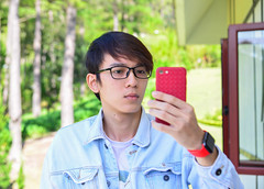 Asian young man making selfie by smartphone (phuong.sg@gmail.com) Tags: adult asia asian attractive background beautiful camera casual cheerful chinese closeup confident expression face fun funny guy handsome happiness happy holding japanese lifestyle male man men mobile outside people person phone photo photograph photography picture portrait self selfie smart smartphone smile taking technology tourism tourist travel vacation young