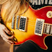 Attractive rock girl with beautiful hair playing Gibson Les Paul closeup