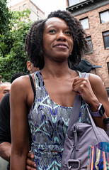 At the Pride Parade (UrbanphotoZ) Tags: prideparade woman smile bag dress watch dreads apartmentbuilding nyc newyorkcity ny newyork tree chelsea manhattan westside