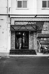 Welcome baby (Go-tea 郭天) Tags: qingdao shandong photography welcome baby sign signboard shop entrance steps stairs door push pushing man client customer enter entering frame framed back business studio street urban city outside outdoor people candid bw bnw black white blackwhite blackandwhite monochrome naturallight natural light asia asian china chinese canon eos 100d 24mm prime in out alone lonely walk walking