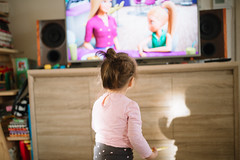 Little girl standing and watching television at home (shixart1985) Tags: family familly education home living room tv television fun funny happy girl baby young back cartoon colorful closeup alone childhood time looking barbie channel cute female speakers music wooden decor
