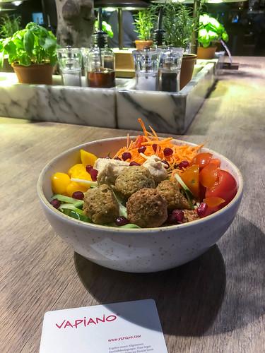 Veganes Essen beim italienischen Restaurant Vapiano mit Falafel, Hummus, Salat, Gemüse und Mango in einer weißen Schüssel