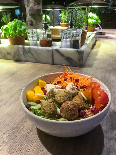 Vegane Rezepte: Bowl mit Falafel, Hummus, Mango, Kirschtomaten, Karotten, Romanasalat, Gurken und Granatapfelkernen