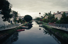 Venice Canals (Past Our Means) Tags: kodak kodakportra portra portra400 400 film filmisnotdead filmphotography travel venice canal canals beach california canon canonae1 river analog analogue reflection morning boat boats palm tree iconla istillshootfilm adventures adventure ca los angeles