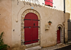 Two red doors (Tiigra) Tags: france 2019 bouchesdurhône vauvenargues door plant color village medieval porch portal architdetail wood arch