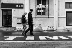 Tim(e) (Go-tea 郭天) Tags: qingdao shandong old men 2 together friends walk walking alley time sign painted painting road lines monsters family fun funny design decoration art signboard windows puddle water rain wall door street urban city outside outdoor people candid bw bnw black white blackwhite blackandwhite monochrome naturallight natural light asia asian china chinese canon eos 100d 24mm prime