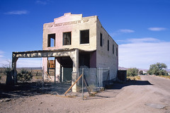 ludlow mercantile. mojave desert, ca. 1999. (eyetwist) Tags: eyetwistkevinballuff eyetwist mojavedesert route66 ludlow abandoned building architecture nikon n90s sigma 2470 f28 nikonn90s sigma2470f28exdg sigma2470mmf28 ishootfilm ishootfuji fuji velvia rvp film emulsion analog analogue mojave desert dry arid hot california southwest lonely scansfromthearchives highdesert usa roadtrip 1999 american west route 66 murphybrothers store ludlowmercantile mercantile 1908 collapsed hectormine earthquake santafe atsf derelict decay gone old historic 35mm fence