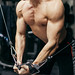 Handsome sportsman doing chest exercise with machine. Body closeup.