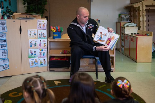 A Sailor reads a book to children at Erickson Elementary School during Tucson Navy Week.