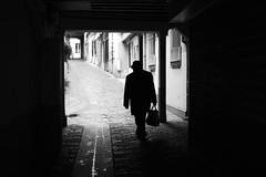At the entrance of the alley (pascalcolin1) Tags: paris homme man ruelle alley pavés pavement sac bag lumière light ombre shade photoderue streetview urbanarte noiretblanc blackandwhite photopascalcolin 50mm canon50mm canon