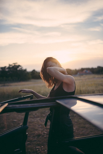 Hipster girl looking out from a vintage car during the sunset.