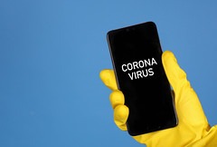 Hands in yellow rubber gloves holding mobile phone with Coronavirus text