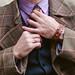 Stylish man in vintage coat adjusting necktie.