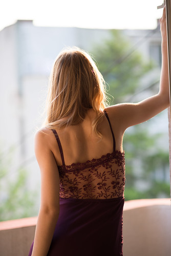 Back view of young woman standing on the balcony.