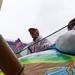 Mann in Stars and Stripes Anzug mit Regenponcho auf einem Persiflagewagen beim Rosenmontagsumzug in Köln