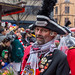 Carnival in Cologne: man in traditional hat and jacket wearing many pins with symbols of the city of Cologne at the Rose Monday parade
