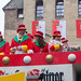 Carnival 2020 in Cologne: the float of the Große Kölner carnival society 1882 with people in red and green costumes throwing sweets and roses to the audience in front of Severinstorburg