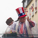 Persiflagewagen beim Kölner Karneval 2020: ein Mann im Stars and Stripes Anzug und Zylinder wirft Kamellen (Süßigkeiten) ins Publikum