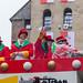 Rosenmontag in Köln: Frau in rot-grün-gelbem Kostüm mit rotem Zylinder wirft Kamellen ins Publikum zusammen mit anderen Mitgliedern der Große Kölner Karnevalsgesellschaft 1882
