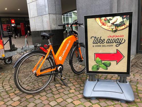 Schild für Take-Away und Home Delivery bei Vapiano und Lieferando E-Bike für Lieferungen