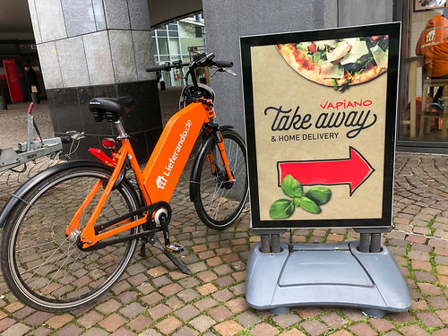Take away and home delivery at Vapiano restaurants: poster and e-bike of food delivery service Lieferando