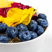 Breakfast with oatmeal, blueberries, pitahaya, pineapple and flowers