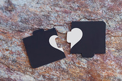 Broken heart made of two pieces of jigsaw puzzle on the marble. Broken heart, loneliness, divorce and unhappy relationships concepts