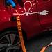 Elektrofahrzeug mit Glühbirnesymbol wird aufgeladen