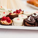 Variety Of Sweet Cakes With Coffee, Rasberries And Cream