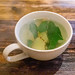 Hot ginger root tea with lemon and mint in a white cup on a wooden table