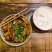 Vietnamesiches Gericht, gesund und vegan: Đậu Hũ Sốt Me - Bio-Tofu in Würfeln, gebraten mit Möhren, Zwiebeln, braunen Champignons, Shiitake-Tamarinde-Sauce und Kräuter, mit Duftreis serviert. Aufnahme von oben